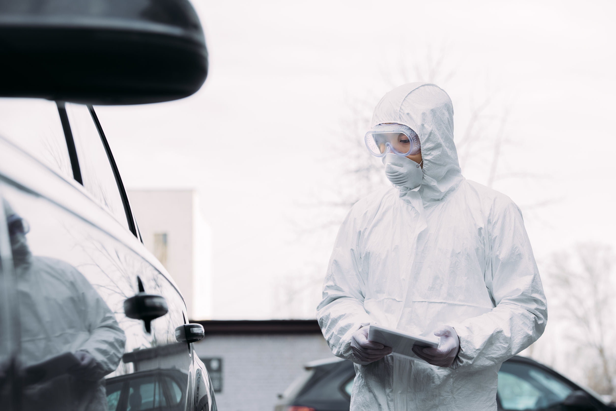 selective focus of asian epidemiologist in hazmat suit and respirator mask holding digital tablet while inspecting vehicles on street